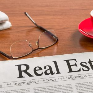 A newspaper on a wooden desk – Real Estate