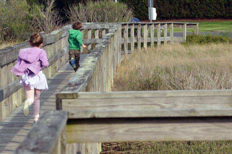 Luce and Theo running on boardwalk