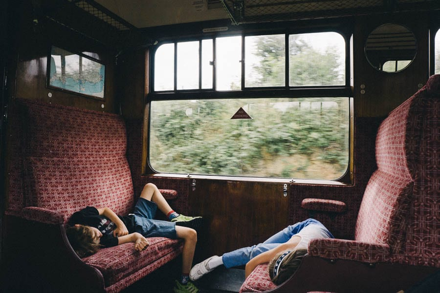Luce and Theo lying on train seats