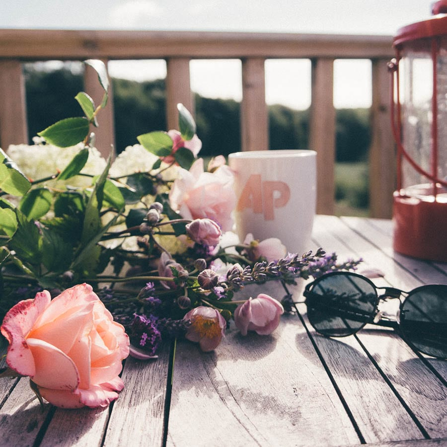 Summertime Flowers and sunglasses on deck table