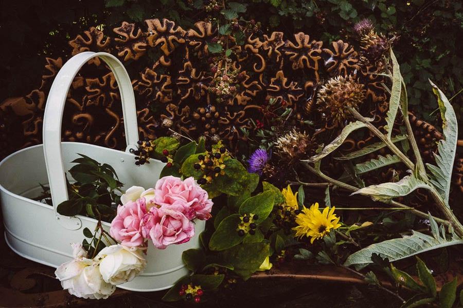 Roses flowers artichokes on garden bench