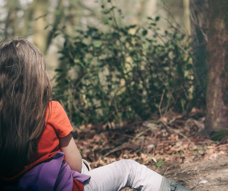 Spring Picnic child sitting in woods