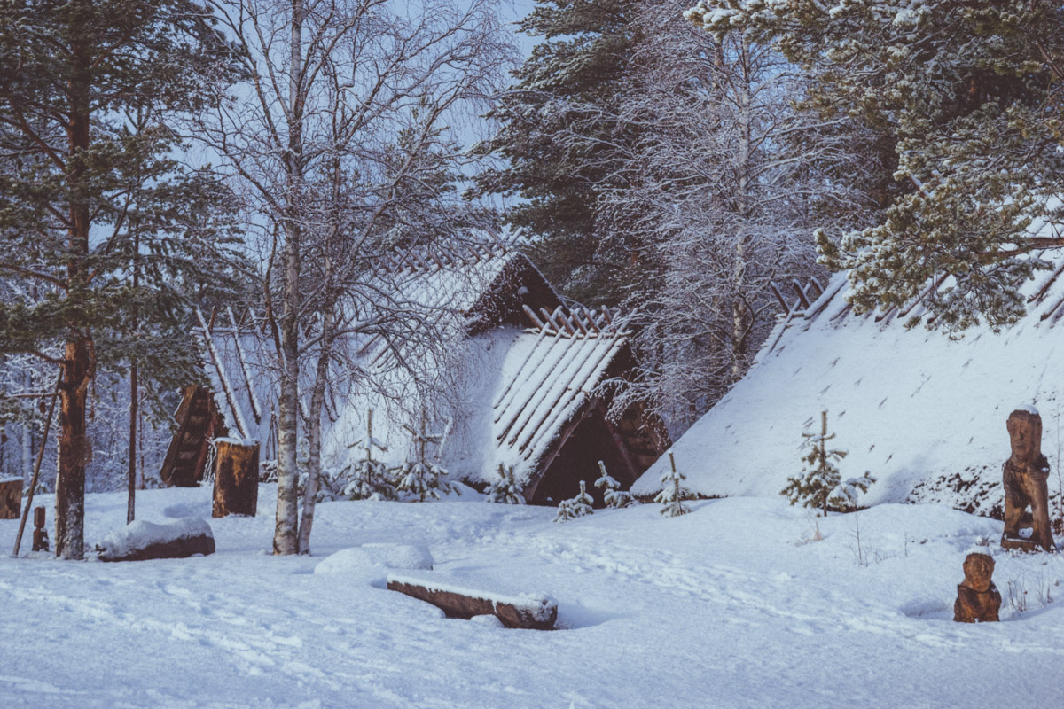 stone age village covered in snow and surrounded by trees
