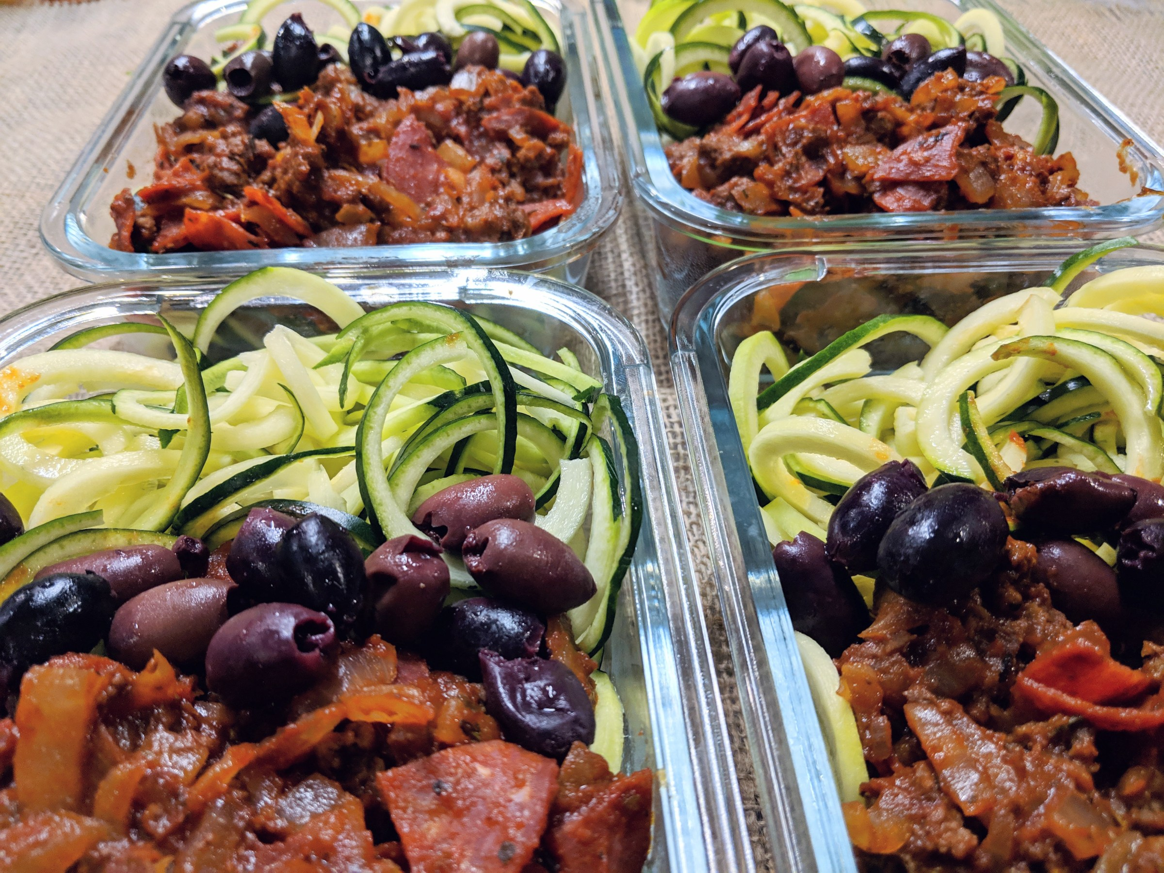 finishes Pizza Zoodles in meal prep containers