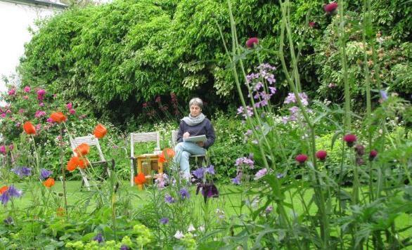 Artist Katherine Cowtan sketching in her garden