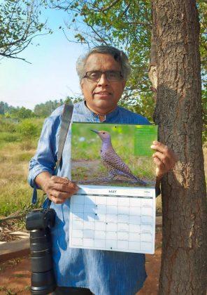 Photo of K Bala holding the 2020 Coast Salish Bird Calendar featuring his photo of a male Northern Flicker.