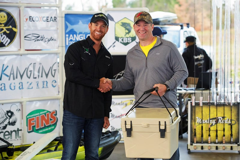 two men smiling and holding a bison cooler