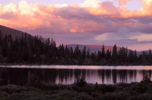 A storm clears in the Uinta mountains. Sunset paints the ragged clouds in hues of pink and purple.