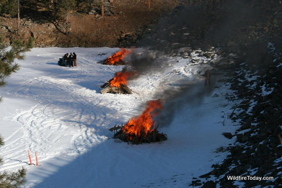 Burning piles on the frozen Lake Pactola.