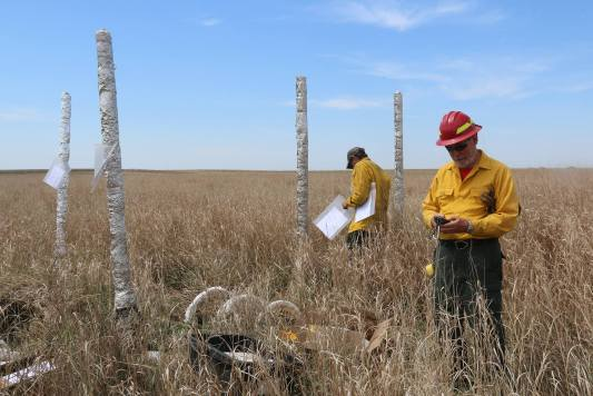 North Carolina State University Joe Roise (foreground) and Bobby Williams (background) set up their fire shelter test site within the Eyecamp prescribed fire area. The sensor poles shown here measure and record the temperature at 2, 4, 6, and 8 feet in height as the fire passes through the area. Photo courtesy Great Plains Fire Management Zone.