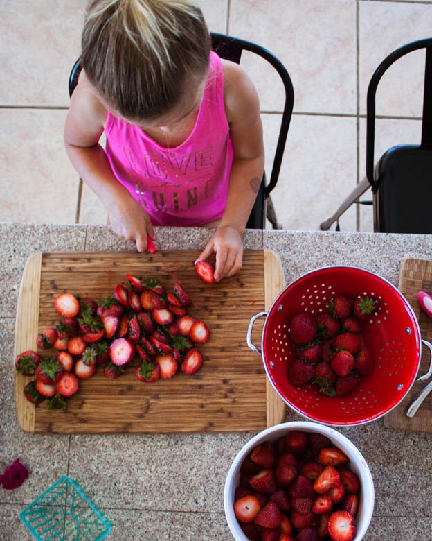 girl cutting strawberries