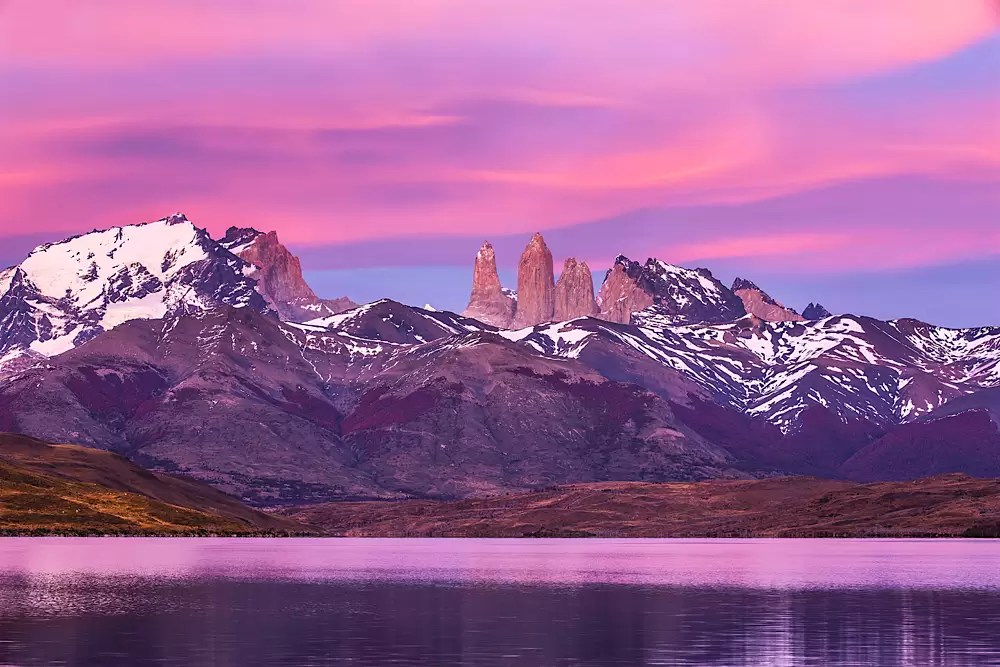 The peaks of Torres del Paine at light of dawn on a lake, reflection