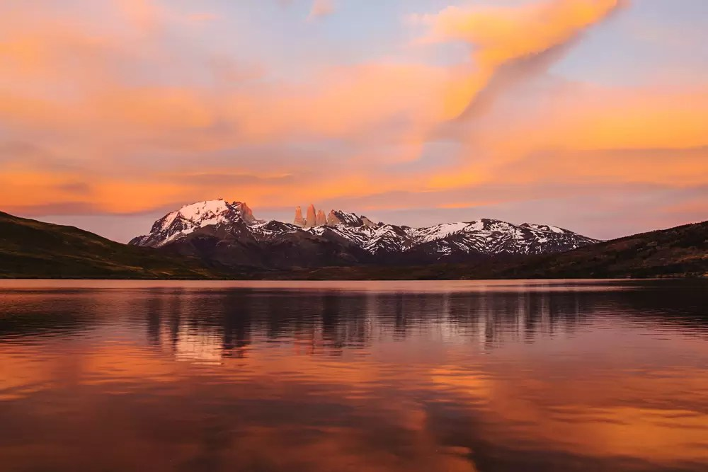 The peaks of Torres del Paine at light of sunrise on a lake, reflection