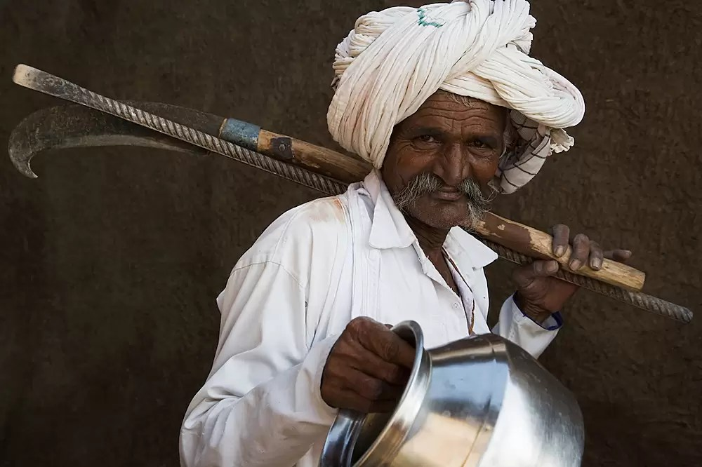 Old Gujarat man carrying tools and water jug