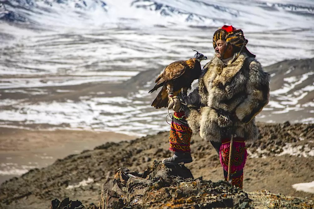 A proud eagle hunter holding his golden eagle while standing on a rocky cliffside overlooking a snowy landscape