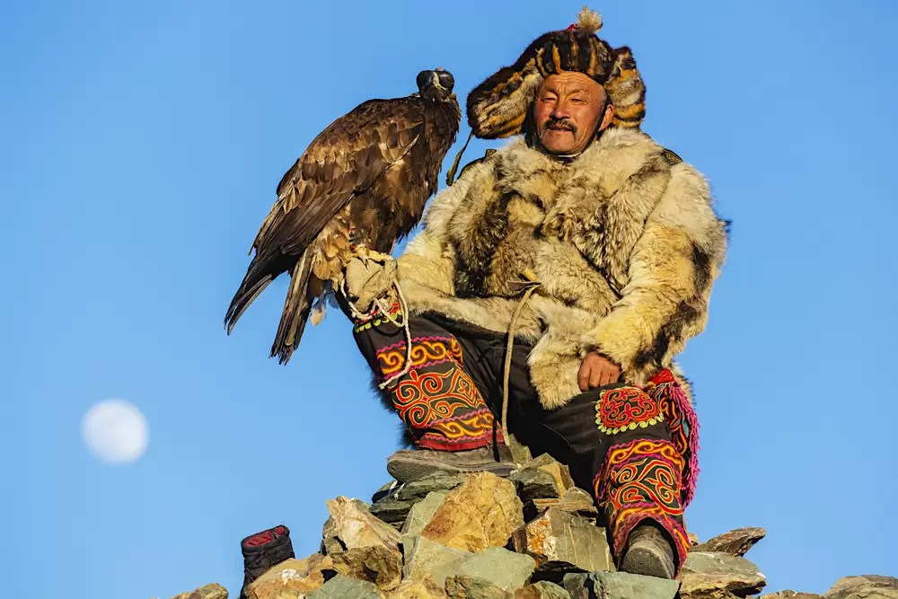 A golden eagle Master holding his golden eagle early in the morning with a full moon