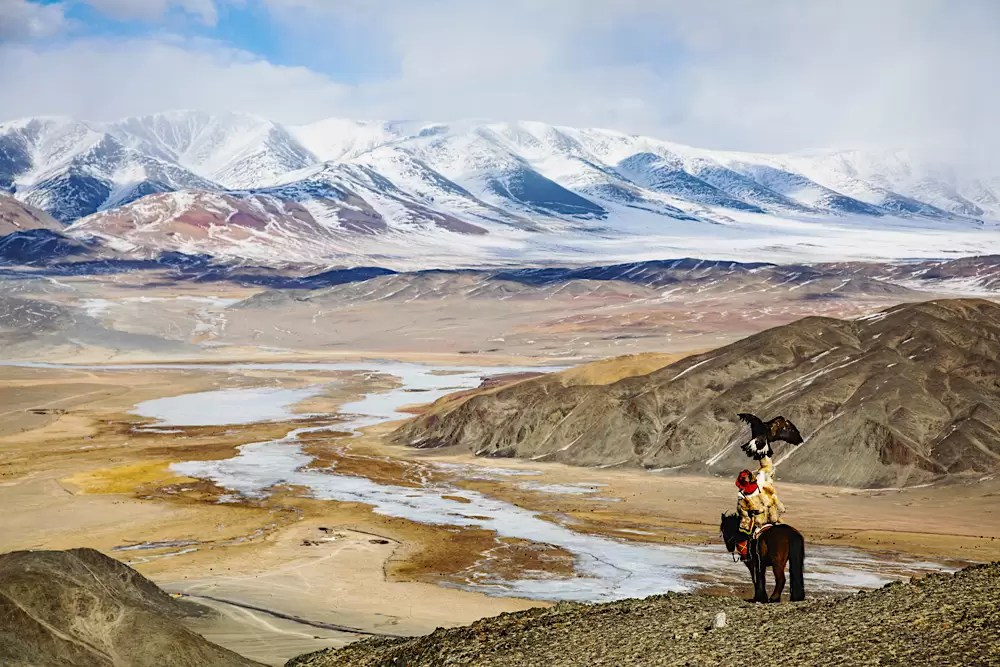 An eagle hunter hunting with his golden eagle on horseback overlooking a cliff trying to find prey