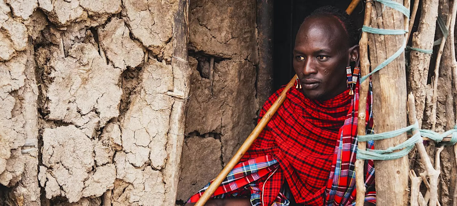 A Morani warrior from the Maasai tribe sitting in doorway of his hut