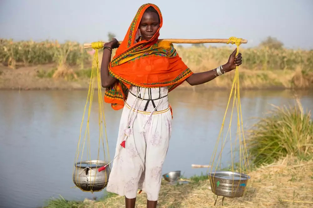 Young Chadian woman collecting water from river