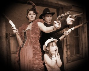 Old time photo with a saloon girl, a cowboy, and a little girl.