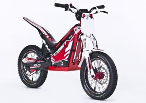 """Have you ever wanted to just ride right out of your garage or build a makeshift course in your backyard? Well, Oset bikes has made this possible without getting your neighbors all in an uproar. The 2016 20.0 48v Racing Electric Trials Bike is designed for 8-12 year old's (but don't let that stop you from trying it out if you're North of that age by 25-30 years) and is powered by 48v battery system (four 12 volt batteries), that has lasted us up to 2-3 hours per ride time, depending on size of rider and how it is ridden. The Oset 20.0 bike comes with a 48v wall charger that takes up to four hours to charge when unit is fully drained. The 20.0 2016 model comes with three fully adjustable power settings (speed, power, and response). Each setting can be adjusted via a knob near the front of the machine. What I have learned is that """"speed"""" is the overall top speed the Oset 20.0 will go, """"power"""" is much like a torque adjustment similar to bottom end on a gas powered machine, and """"response"""" is how quick you want the throttle to hit when accelerating (similar to rpm response on a gas powered machine). For those in the target age range, the Oset 20.0 is a machine, which is a lot of fun, provides incredible opportunities for gaining skills, and the bike can be ridden in a decent-sized backyard – without upsetting your not so dirt bike friendly neighbors. The Oset 20.0 machine is configured with front and rear disc brakes controlled by hand levers, like a mountain bike, a twist throttle like a motorcycle, and the direct-drive electric motor means there's no transmission, so no shift lever or clutch."""