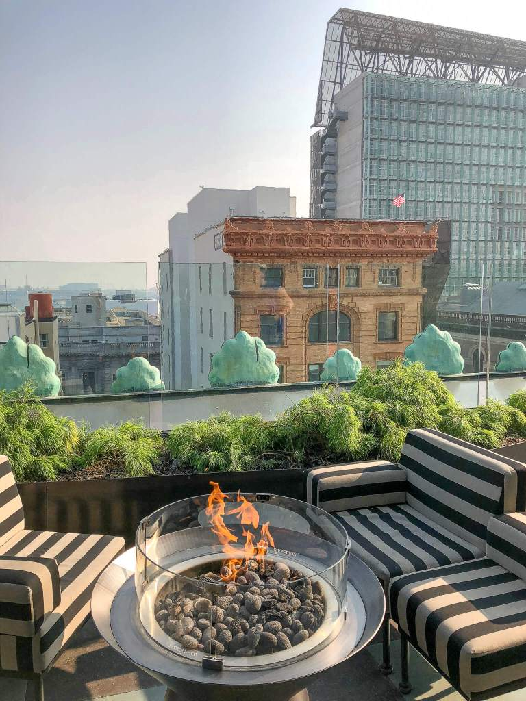 The rooftop terrace on the Proper Hotel is filled with black and white striped couches and firepits, overlooking the city.