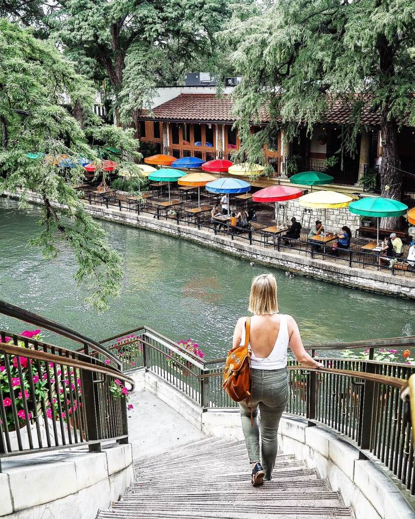 Dana is walking down a curved staircase in San Antonio, to the riverwalk which is dotted with colourful umbrellas