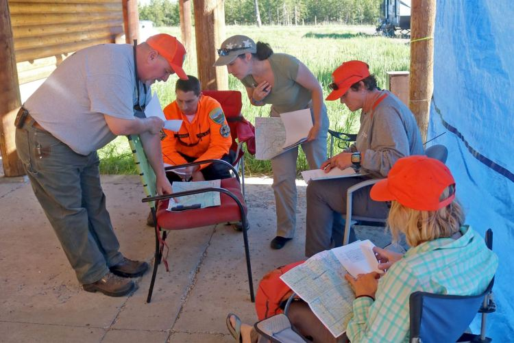 """Wallowa County SAR incident commander Matt Howard (left) goes over plans for the Sunday, June 27 search exercise with WCSAR volunteers. All four would be the """"lost"""" people that SAR teams had to """"rescue."""" Photo: Traci Murray."""