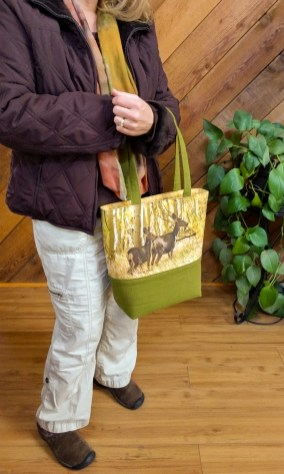This handmade tote bag by Wild Onion Creations features a doe and fawn foraging in the glow of the fall colors aspens and is ready to corral all your stuff to keep you organized throughout your day
