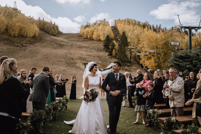 Bride and groom celebrate getting married walking down the aisle to their guests on a ski hill with no snow and a chair lit in the background