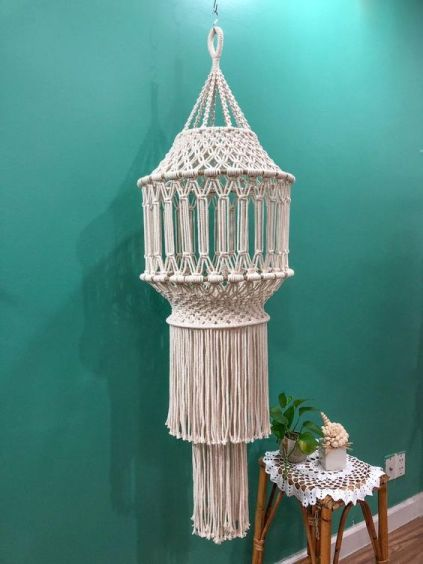 Macrame lantern hanging on a green wall