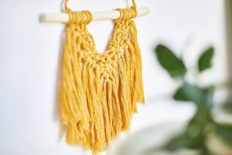 yellow macrame hanging on a white wall