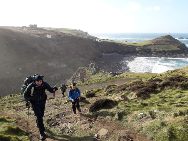 Walkers climbing the South West Coast Path with Cape Cornwall in the background