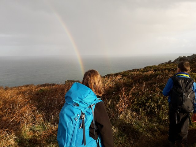 Two children wearing backpacks looking at a rainbow out to sea.