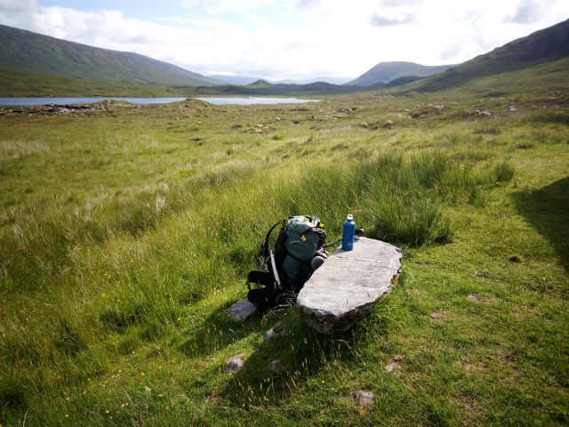 stone seat with backpack in wilderness