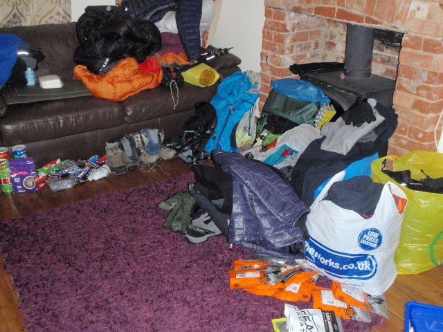 lounge with walking kit, clothes and sleeping bags laid out ready to pack