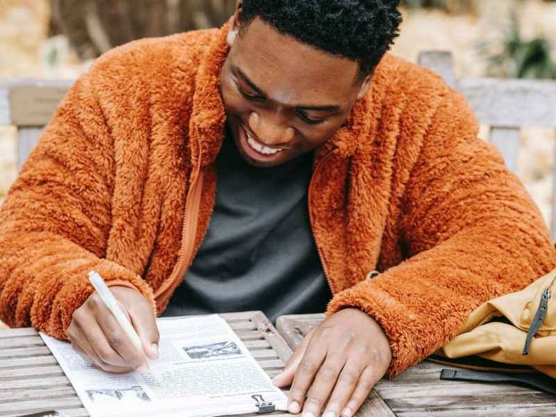 young black man working with report and outlining text