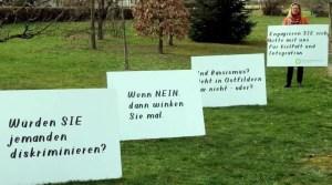 Ursula Zitzler mit Plakaten gegen Rassismus auf einer Wiese