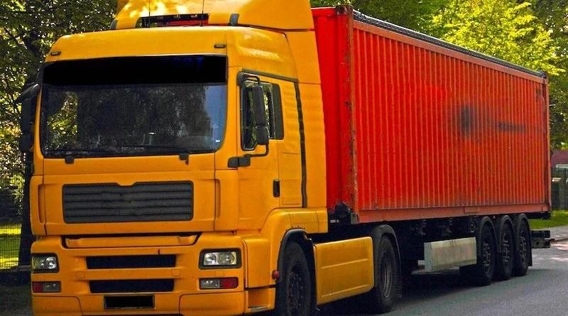 gelber LKW Sattelschlepper mit rotem Überseecontainer