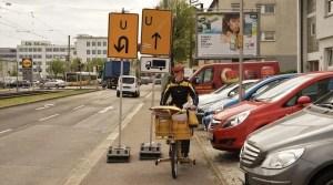 Postbotin auf dem Rad umkurvt Umleitungsschilder