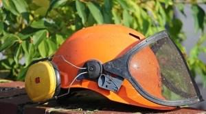 orange Schutzhelm mit Sichtschutz vor Hecke
