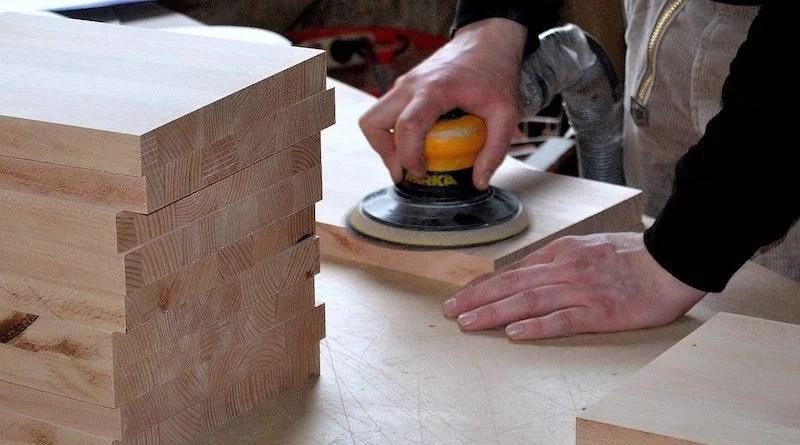 Schreiner schleift mit Maschine ein Holzbrett