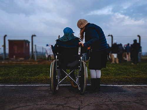 woman in wheelchair and caregiver at park