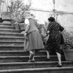 Image of two older women walking up stairs for an article about what is a lift chair and who can benefit from using one.