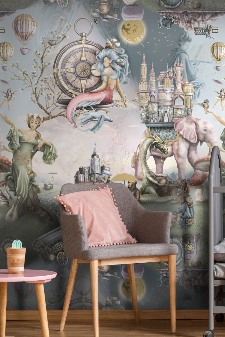 This is luxury designer fairytale wallpaper wall mural design from Australia. It is shown here in a girls bedroom nursery and has been styled with a grey cot, pink side table grey pink and gold wood chair.