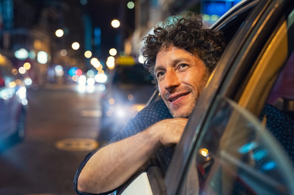 Man smiling looking out of a car window in the city after going to therapy | Willow Counseling | Nashville, TN