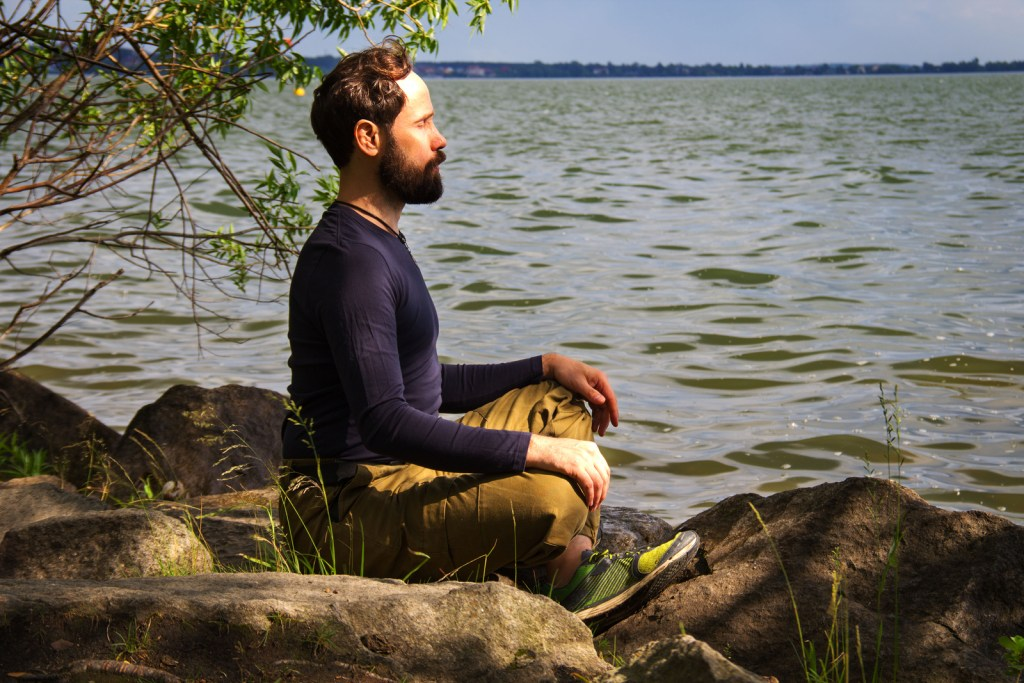 Bearded man meditating by lake | Counseling for stress and anxiety in Nashville TN | Willow Counseling
