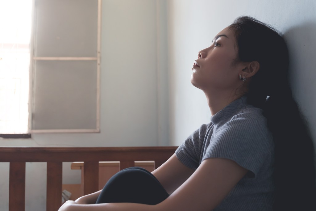 Asian woman looking at a wall feeling numb when thinking about her childhood sexual abuse and the sexual assault she suffered as an adult.  She has PTSD and is considering EMDR therapy with a trauma therapist in Nashville, TN