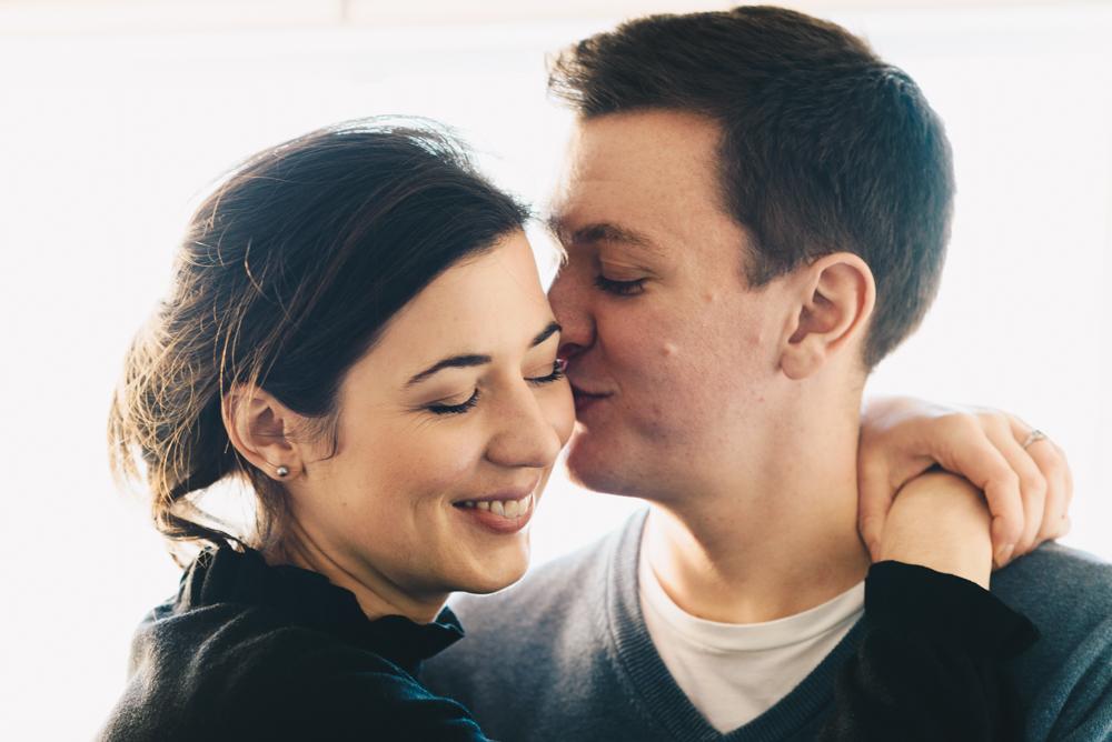 man kisses fiancee on cheek