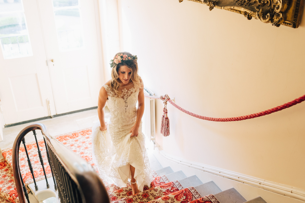 Bride walks up stairs on the way to her wedding ceremony